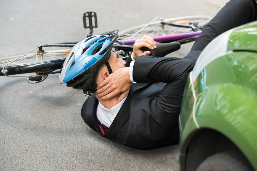 A cyclist knocked off his bicycle by a car driver