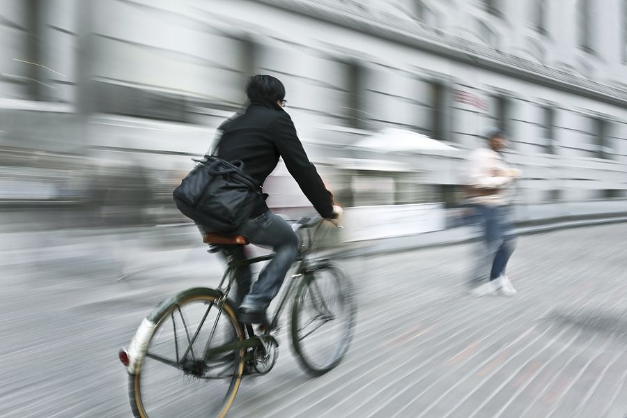 A bicycle heading towards a pedestrian who has stepped into the street without looking