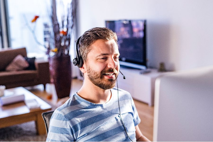 A man working from home, wearing a video conferencing headset