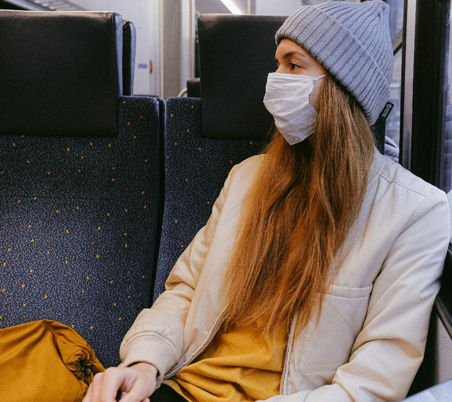 A young woman on a train wearing a COVID-19 face mask