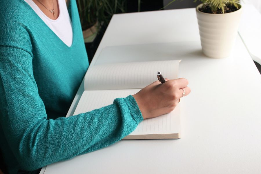 A woman sitting at a table signing a document